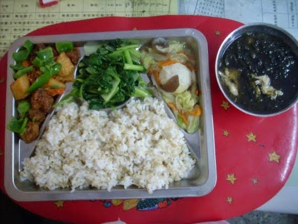 Country: Taiwan Contents: On the left: sweet and sour pork with pineapple, radish, carrots and green pepper, middle: vegetable stir fry with garlic, on the right: fish ball stew with cabbage, carrots and wood ear mushroom, and soup: seaweed and egg drop.