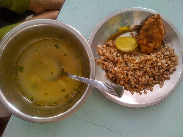 Country: Buchach, Ukraine (primary and secondary school) Contents: Soup with potatoes, buckwheat, cutleta (sausage patty), and a pickle.