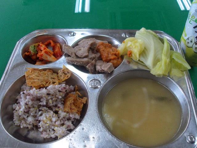 Country: South Korea Contents: Kimchi, pork, bean paste sauce (sammjang), steamed cabbage, soup.