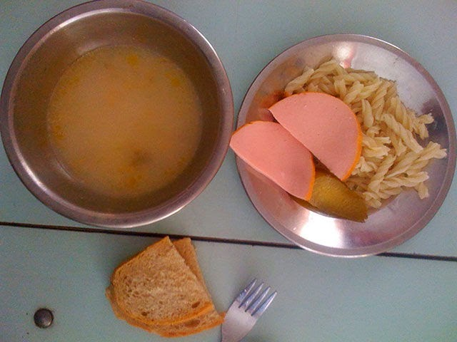 Country: Buchach, Ukraine Contents: Soup, macaroni, pickle, bread, sliced hot dog.